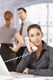 Young secretary on the phone in office. Young secretary using landline phone in office, young people chatting in background Royalty Free Stock Images