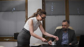 Young secretary servicing the coffee to her handsome boss stock video