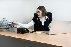 Young secretary with  telephone and laptop Royalty Free Stock Photos