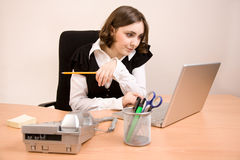 Young secretary with telephone, laptop. And pencil working at office stock photography