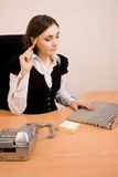 Young secretary with telephone and pencil. Young secretary with telephone, laptop and pencil thinking stock image