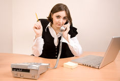 Young secretary with telephone and pencil. Young secretary with telephone, laptop and pencil calling by phone royalty free stock images