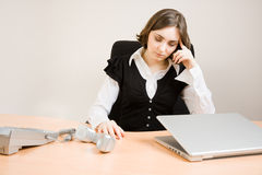 Young secretary with  telephone and pencil Royalty Free Stock Images