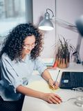 Young secretary with wavy hair working in front of laptop. Writing reports to chief, boss Stock Images