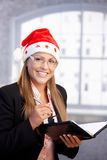 Young secretary wearing santa hat smiling Royalty Free Stock Photo
