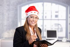 Young secretary wearing santa hat smiling. Young secretary wearing santa hat, holding appointment book, smiling in office Royalty Free Stock Images