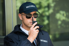 Young Security Guard Talking On Walkie-talkie stock image