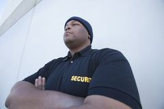 Young Security Guard By Wall. Young security guard with arms crossed standing by the wall stock photography