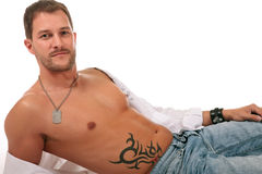 Young seductive caucasian man. Lying down and showing his beautiful naked chest. Studio shot. White background Royalty Free Stock Photography