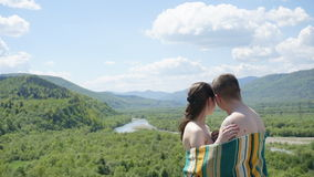 Young seductive naked couple covered by blanket softly embrasing on the green mountains background Stock Photo