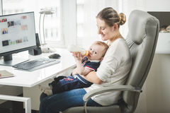 Young self employed mother working at home and taking care of he. Portrait of young self employed mother working at home and taking care of her baby Stock Images