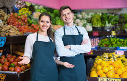 Young sellers having vegetables and fruits on displays. Friendly young sellers having vegetables and fruits on displays of market royalty free stock photos