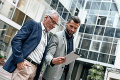 Young and senior business men using digital tablet outdoors on the city background Stock Image