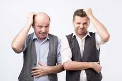 Young and senior businessman scratch their heads, confused, thinking about something. Having troubles at work stock photos