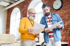 Two economists. Young senior economists or analysts in casualwear discussing financial papers at working meeting royalty free stock image