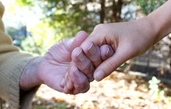 Young and senior holding  hands Stock Photo