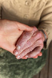 Young and senior holding  hands Royalty Free Stock Image