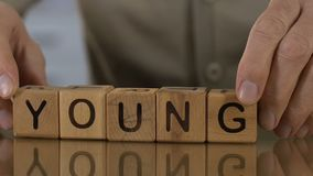 Young, senior man making word of wooden cubes, memories, desire to be younger. Stock footage stock video