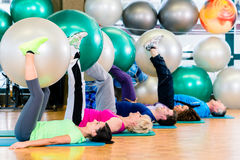 Young and senior people exercising with ball in gym Stock Photo
