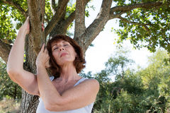 Young senior woman in meditation with a tree for serenity Royalty Free Stock Photo