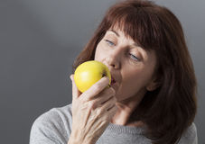 Young senior woman thinking in biting into golden apple Stock Photo