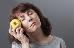 Young senior woman touching her face with golden apple for skin softness. Diet and food concept - sleepy beautiful mature woman holding yellow apple for veggie Royalty Free Stock Photography
