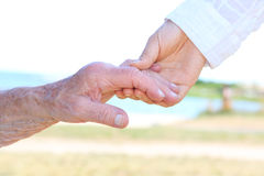 Young and senior women holding hands Stock Photo