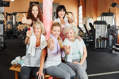 Young and senior women holding thumbs up stock photo