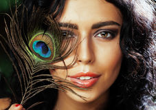 Young sensitive brunette woman with peacock feather eyes close up on green smiling, lifestyle people concept stock images