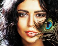 Young sensitive brunette woman with peacock feather eyes close u stock photos