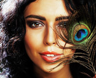 Young sensitive brunette woman with peacock feather eyes close up royalty free stock images