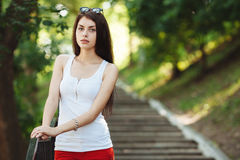 Young sensual beautiful brunette woman posing on the stairs in the summer park Royalty Free Stock Photo