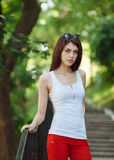 Young sensual beautiful brunette woman posing on the stairs in the summer park Stock Images