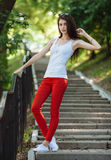 Young sensual beautiful brunette woman posing on the stairs in the summer park Royalty Free Stock Images