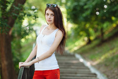 Young sensual beautiful brunette woman posing on the stairs in the summer park. Young sensual beautiful brunette woman having fun on the stairs in the summer Stock Photography