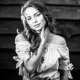 Young sensual & beauty girl in stylish dress pose against grunge wooden background. Black-white photo Royalty Free Stock Photography