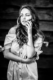 Young sensual & beauty girl in stylish dress pose against grunge wooden background. Black-white photo Stock Images