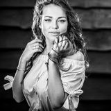 Young sensual & beauty girl in stylish dress pose against grunge wooden background. Black-white photo Stock Photography