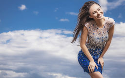 Young sensual & beauty woman in a fashionable dress pose outdoor on sky background. Stock Photography