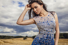 Young sensual & beauty woman in a fashionable white-blue dress pose on field. Royalty Free Stock Photo