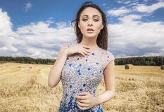 Young sensual & beauty woman in a fashionable white-blue dress pose on field. Royalty Free Stock Image