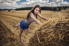 Young sensual & beauty woman in a fashionable white-blue dress pose on field. Stock Image