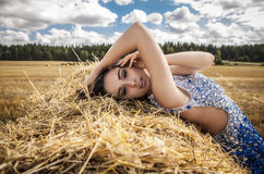 Young sensual & beauty woman in a fashionable white-blue dress pose on field. Royalty Free Stock Images