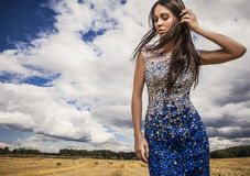 Young sensual & beauty woman in a fashionable white-blue dress pose on field. Stock Photo