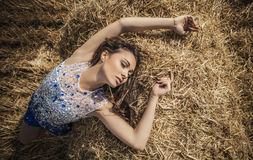 Young sensual & beauty woman in a fashionable white-blue dress pose on field. Stock Photos