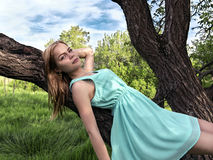 Young sensual blonde girl lying on a tree branch Royalty Free Stock Image