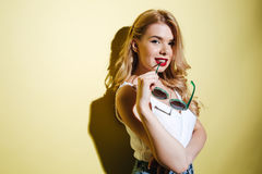 Young sensual blonde woman holding sunglasses and looking at camera Royalty Free Stock Images