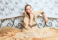 Young sensual blonde woman in vintage dress sitting on the bed Stock Photography