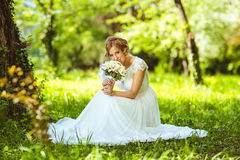Young sensual bride sitting in a summer. Field with white flowers royalty free stock photos