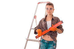 Young sensual brunette woman in uniform makes renovation with ladder looking at the camera isolated on white background Royalty Free Stock Photography
